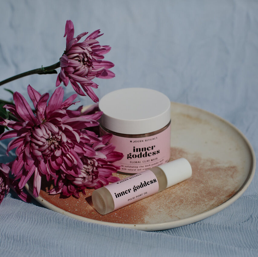 modern rituals essential oils on a tray with flowers